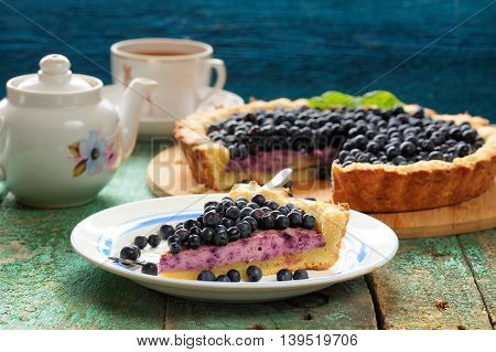 Yummy homemade open pie with cream cheese filling and fresh forest blueberries closeup