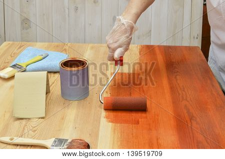 person painting a table with cherry colored varnish