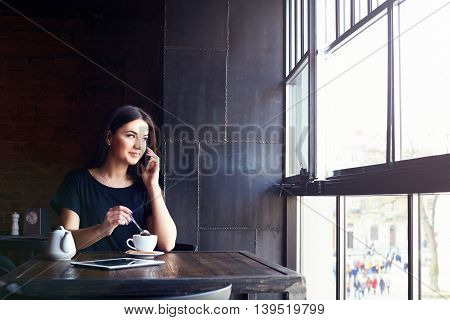 Young Attractive Girl Talking On Mobile Phone In Coffee Shop