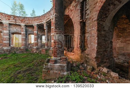 Ancient rotunda with columns without a dome. The brick ruins of the interior of an abandoned temple overgrown with grass