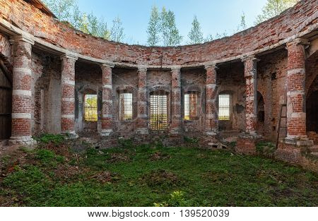 Ancient rotunda with columns without a dome. Abandoned brick temple overgrown with grass