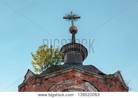 Metallic cross with a Masonic symbol on the dome of an abandoned temple