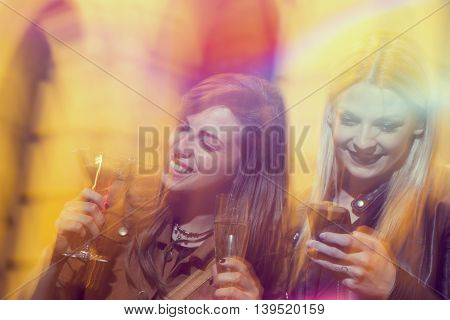 Two girl friends drinking cocktails and having fun on a girls' night out