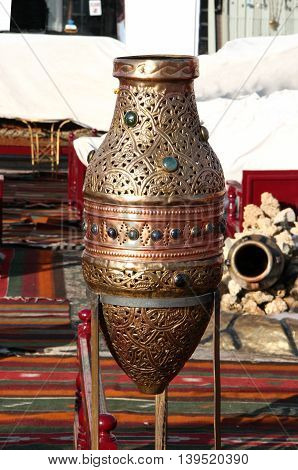 carved metal jug decorated with stones on a metal stand