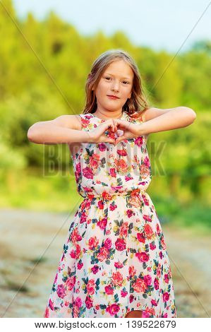 Outdoor portrait of a cute little girl of 8 years old making heart shape form by her hands. Pretty kid girl playing outdoors at sunset