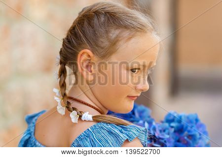 Summer portrait of a cute little girl with blue hydrangea flowers