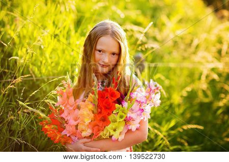 Golden hour portrait of a cute little girl of 8 years old, holding colorful gladiolas flowers