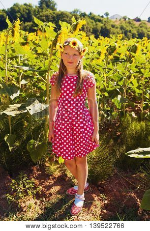 Little girl playing in sunflower fiield on a very hot summer day, wearing red polka dot dress and shoes, yellow flowers headband