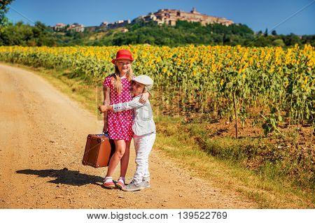 Two cute kids, little girl and brother, walking down the small road by sunflowers field, holding old brown suitcase. Image taken in Tuscany, Italy. Little girl wearing red polka dot dress and shoes