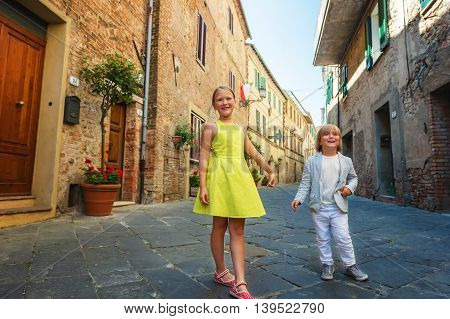 Adorable kids having fun outdoors, dancing on the streets of old italian city