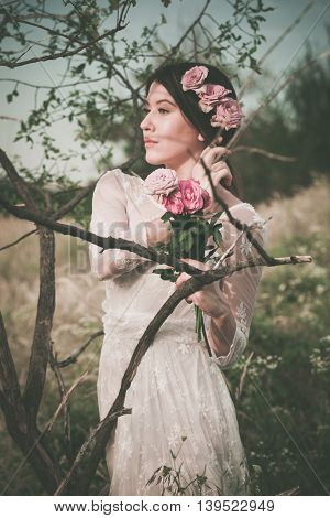 young woman in white lacy  portrait with roses by tree