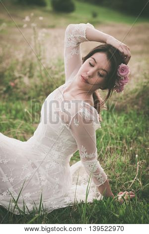 young beautiful  woman in white lacy dress sit on grass with roses in hair