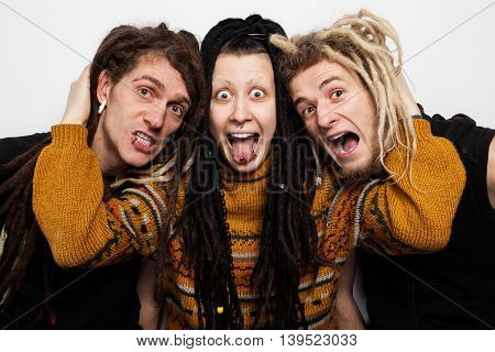 Collective portrait of three freaky people with dreadlocks and piercings aping, white background