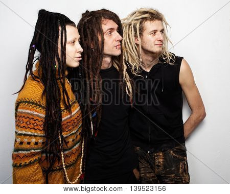 Group portrait of three positive dreadlocks , two boys and a girl, profile view, on white background