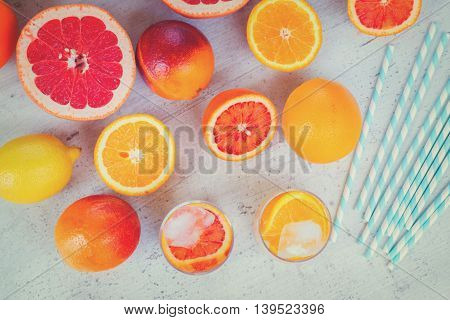 Summer refreshing orange, lemon and greipfruit citrus drinks with ice on white table, retro toned
