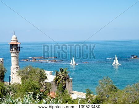 Minaret of Al-Bahr Mosque and White Yacht in blue Mediterranean Sea in old city Jaffa Israel