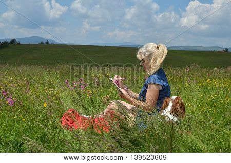 Women Writing In Notepad On A Meadow