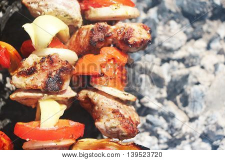 Meat and vegetables frying on a grill on a closeup background of the ash