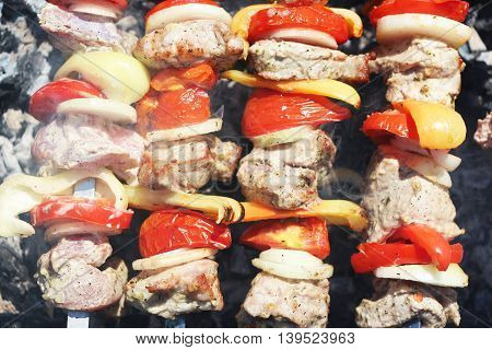 The barbecue cooking. Meat and vegetables tomato, bow, pepper, grilled on charcoal, close-up