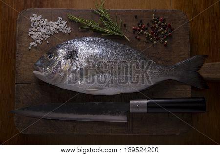 Delicious fresh sea bream fish on a wooden cutting board
