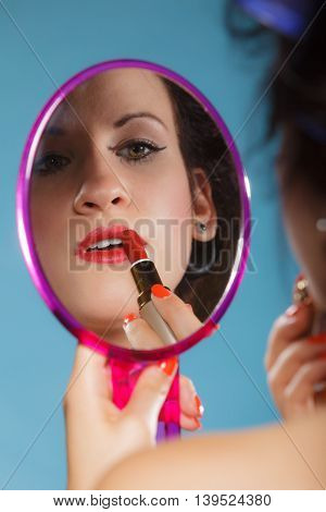 Cosmetic beauty procedures and makeover concept. Closeup part of woman face. Girllooking at mirror applying red lipstick lips makeup