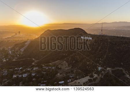 Los Angeles, California, USA - July 21, 2016:  Aerial of sun setting behind the Hollywood Sign on Mt. Lee in Griffith Park.