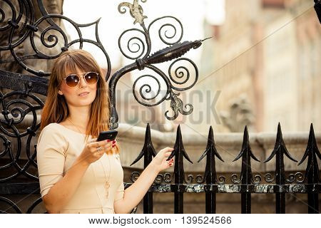 Traveler woman fashion girl with smart phone outdoors in european city old town Gdansk Neptune fountain in the background Poland Europe