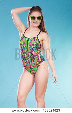Gorgeous young woman girl in swimsuit swimwear and sunglasses on blue. Summer holiday vacation relax.