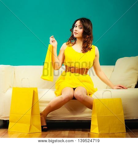 Buying retail sale concept. Fashionable girl yellow dress high heels sitting on couch with shopping bags on green