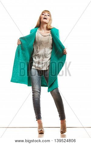 Fashion. Young blonde fashionable woman in full body wearing vivid color green blue wool coat high heels shoes. Female model posing isolated on white
