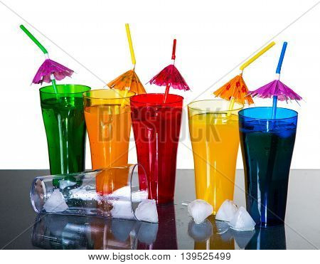 Colored Glasses With Cocktails And Ice Cubes On A White Background