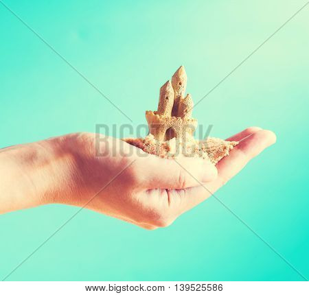 Hand Holding A Sand Castle