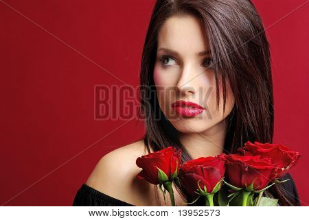 Beautiful woman with a rose over red background