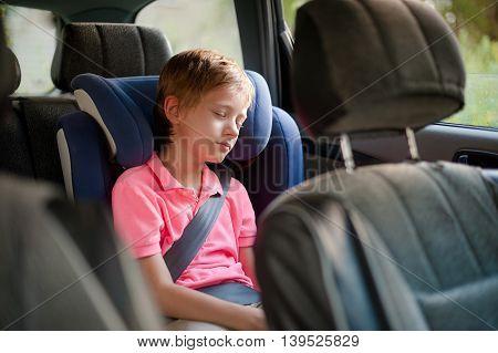 boy in a pink shirt sleeping in car seat