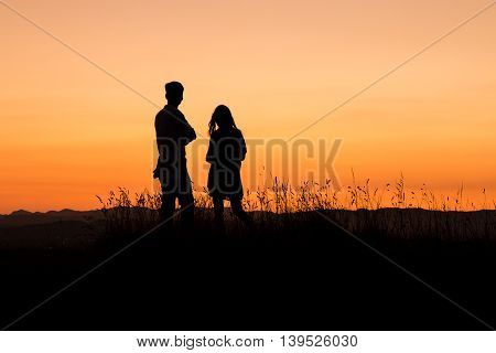silhouette of young couple watching sunset on meadow