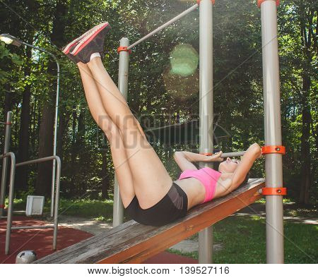 Young Female Sportswoman Doing Abs Exercise On Sports Bench, Outdoor