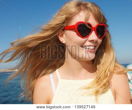Summer happiness and lifestyle concept. Lovely blonde girl in red heart shaped sunglasses relaxing on the sea coast.