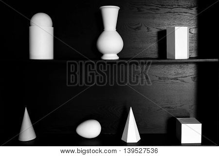 Abstract white plaster geometric shapes for art and decorations on a black tree. Mysterious and unusual design of the walls in the interior. The view of the form.