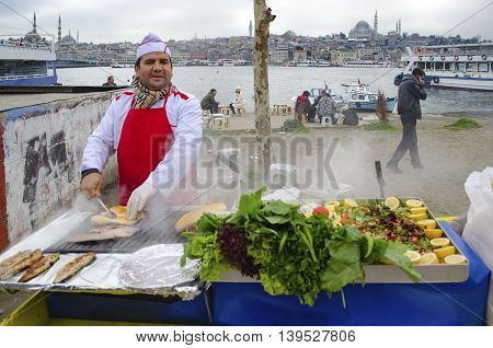 Istanbul Turkey - February 26 2013: Istanbul Golden Horn boats at sea. Grilled fish people who eat fish on the beach bread. Galata bridge and Eminonu looks new mosque in the background.