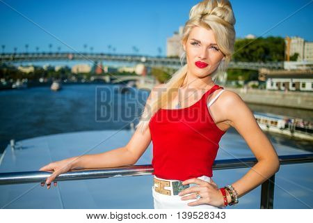 Blonde cute woman in red top on back of ship near bridge over Moscow River