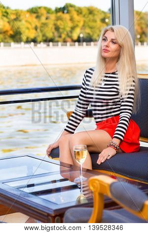 Pretty woman sits on seat in restaurant on sailing ship at sunny day