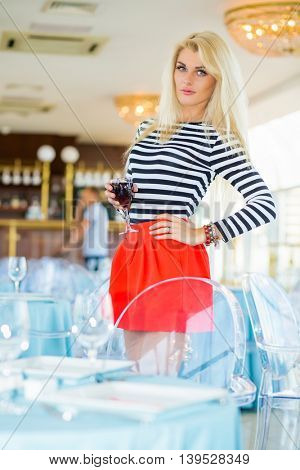 Blonde young woman in striped t-shirt holds glass of wine in restaurant