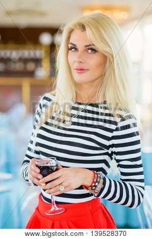 Blonde pretty woman in striped t-shirt holds glass of wine in restaurant