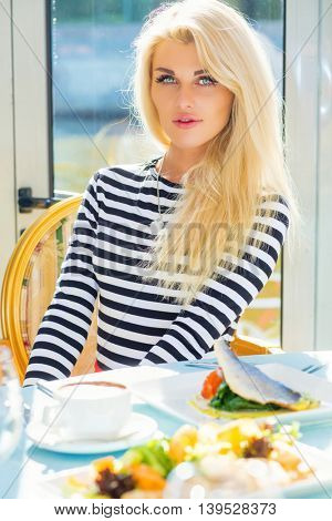 Blonde pretty woman in striped t-shirt sits at table with courses in restaurant