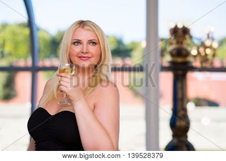 Blonde smiling woman stands in ship restaurant and holds wine glass