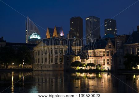 View on Mauritshuis Museum and a part of Binnenhof the Dutch Parliament Building in the Hague the Netherlands at night. In the Background the Skyline of the Hague with Skyscrapers