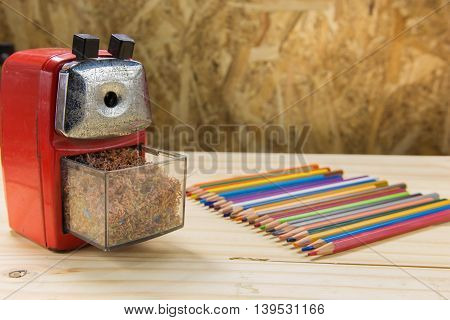 Stationery pencil and sharpener on wooden background .