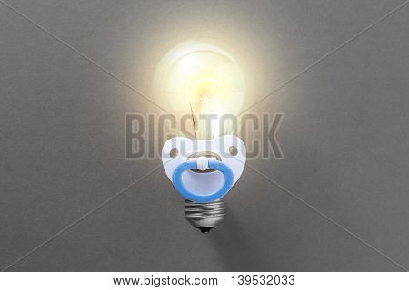 Burning light bulb with pacifier on a gray background. Idea for a startup in the beginning of its development. Concept of a startup
