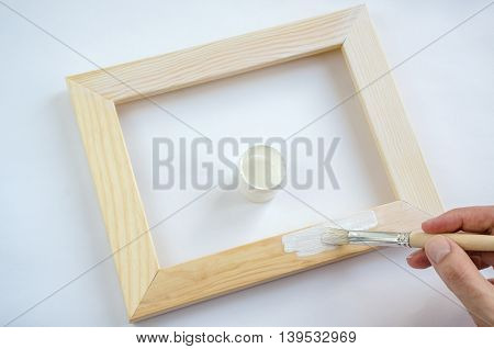 Woman hand painting picture frame on white color