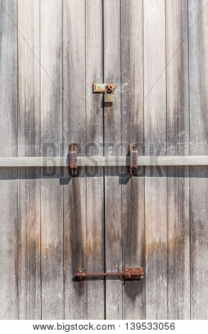 Close up rustic padlock on wooden entrance door in farmland.